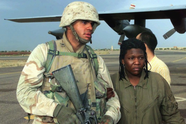 Marine Corps Lance Cpl. Curney Russell from the 3rd Light Armored Reconnaissance Battalion provides a steady arm for former prisoner of war Army Spc. Shoshana Johnson, with the 507th Maintenance Company, at Kuwait City, Kuwait. Johnson and other POWs were rescued in April 2003, after being captured and held by forces loyal to Saddam Hussein.
