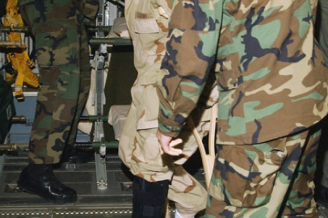 Former prisoner of war Spc. Shoshana Johnson, 507th Maintenance Company, Fort Bliss, Texas, tries out her crutches with help from Air Force medical personnel aboard a C-17A Globemaster III at Ramstein Air Base, Germany, before her trip home to the United States in April 2003.  Johnson was wounded and subsequently captured in an ambush during Operation Iraqi Freedom, March 23, 2003.