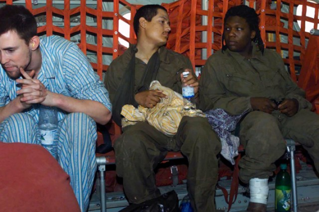 Chief Warrant Officer Ronald Young, left, Spc. Joseph Hudson and Spc. Shoshana Johnson relax aboard a Marine Corps aircraft bound for Kuwait City, Kuwait. The three, along with four other American POWs, were rescued in April 2003, after being captured and held by forces loyal to Saddam Hussein.