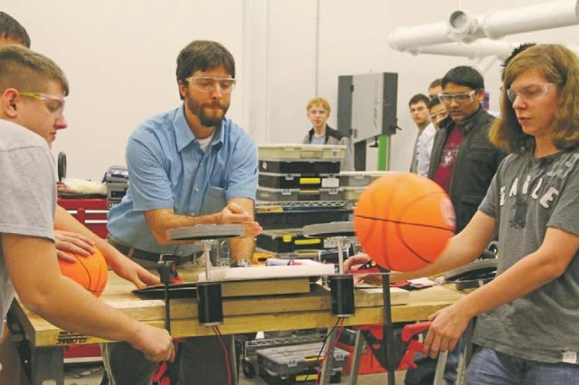 (From left) Spenser Puffenbarger, Marc Evans and Christopher Flake test the robot's firing apparatus. CERDEC engineers mentored the students as they designed and built the robot.