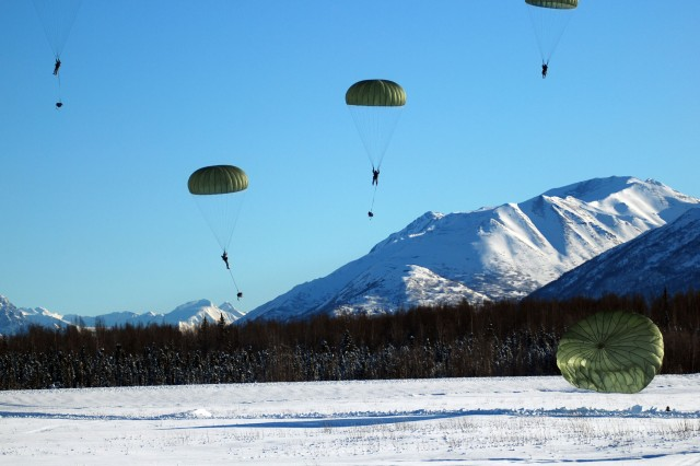 "Paratroopers descend to Malamute Drop Zone on Joint Base Elmendorf-Richardson, Alaska, after performing an exit technique called the ""mass exit"", with aircraft in a trail formation. While relatively close together on the descent, jumpers are trained to maintain a minimum safe distance in the air of 25 feet while jumping with a T-10 Delta parachute."