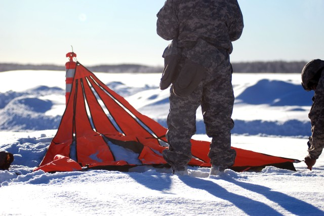 A drop zone safety officer and assistant DZSO set up a raised angle marker at Malamute Drop Zone on Joint Base Elmendorf-Richardson, Alaska. The marker helps pilots to visually confirm the location of the drop and the direction of their approach.