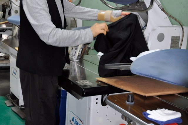 Song Young-sun, a staff member of the Quartermaster Laundry Service on U.S. Army Garrison Yongsan, prepares to press a garment in Seoul, South Korea. Due to a reduction in personnel, the QLS will discontinue individual laundry piece rate services to the Community beginning April 1, 2012. (Photo by Mark Abueg)