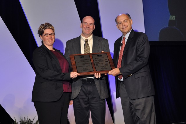 During the recent Defense Manufacturing Conference held in Anaheim, Calif., Anthony Haynes (center), Program Manager for the Aviation and Missile Research, Development and Engineering Center's Low Cost Zinc Sulfide Missile Dome Manufacturing Technology Program and Dr. Teresa Clement, Raytheon Missile Systems, receive the Defense Manufacturing Excellence Award from Rick Jarman, National Center for Manufacturing Sciences. Courtesy photograph