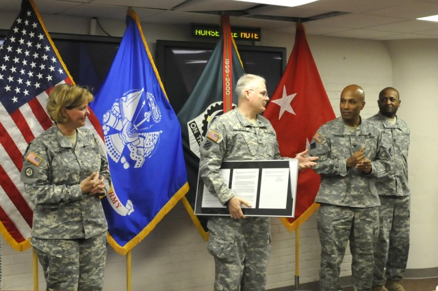 Maj. Gen. Patricia McQuistion, ASC commanding general, looks on as Brig. Gen. Brian Layer, ASC deputy commanding general for sustainment, presents Col. Victor Harmon, commander of the DMC, with a plaque honoring the Lead Materiel Integrator mission transfer, Feb. 29.