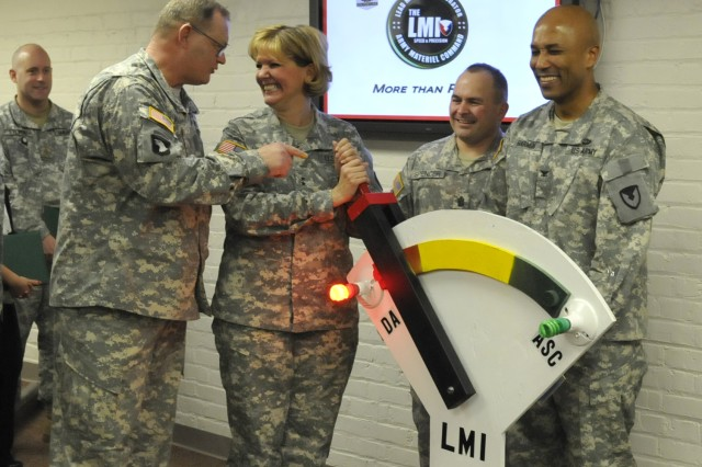Lt. Col. Michael Alsbrook, DMC, shows Maj. Gen. Patricia McQuistion, ASC commanding general, how to work the switch which signifies the transfer of the LMI mission from the Department of the Army to ASC.