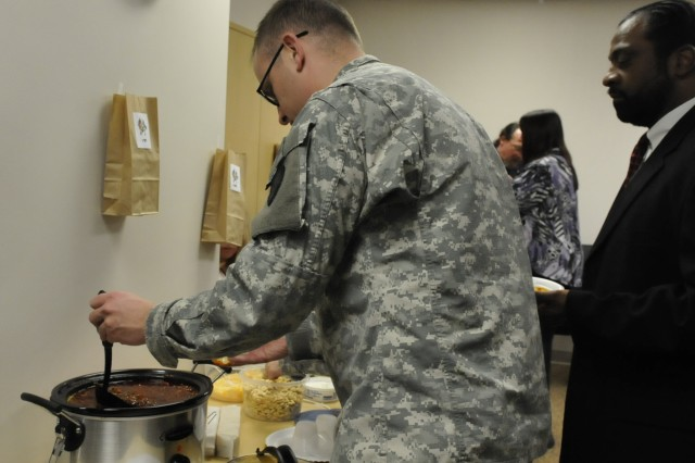 Capt. Andrew Burrows, Distribution Management Center, samples one of the chilies offered during the Feb. 29 Army Sustainment Command Family Readiness Group chili cook-off. The event was held in Building 390 at Rock Island Arsenal and raised money through donations for future FRG events.
