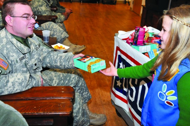 While thanking him for his service, Annabelle hands a Soldier a box of Girl Scout cookies at the Fort Drum USO on Feb. 24.