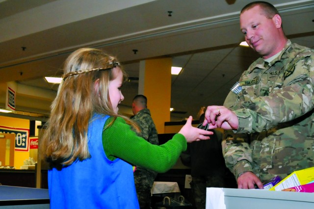 After receiving a box of cookies, 10th Mountain Division (LI) Soldier Staff Sgt. Darrin Hafeli rips the 2nd Armored Cavalry Regiment patch from his right sleeve and gives it to Annabelle as a token of his appreciation.