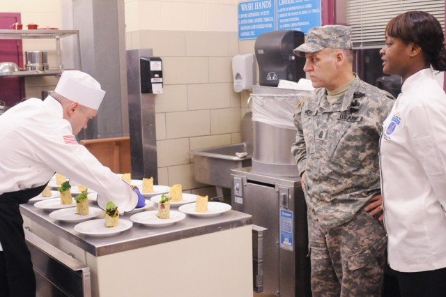 Spc. Markeeshia Neal, far right, talks to Command Sgt. Maj. Rick Merritt, 10th Mountain Division (LI) senior enlisted adviser, about the appetizer plates while Sgt. David Cantwell plates the salad-filled parmesan rolls.