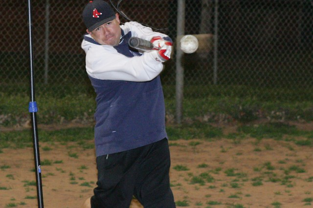 Sgt. Emmanuel Carrillo hits a softball from his hanging batting tee at Butner Field on Fort Sill. He hits about 200 balls a week practicing for the upcoming softball season.