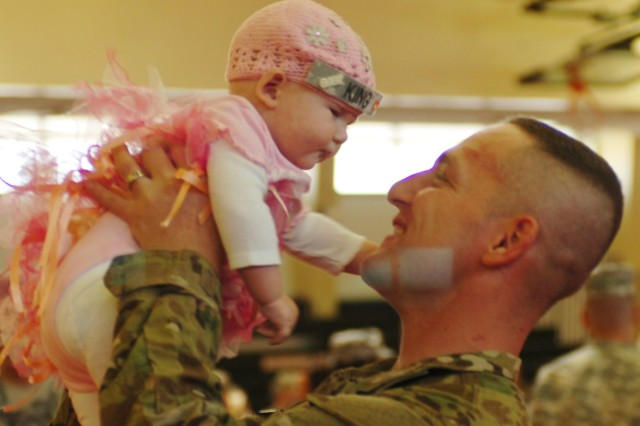 "A Soldier from C Battery, 2nd Battalion, 4th Field Artillery, holds up his daughter at the welcome home ceremony for the battery. ""Charlie Rock"" battery had deployed in August for a six-month security mission in Afghanistan."