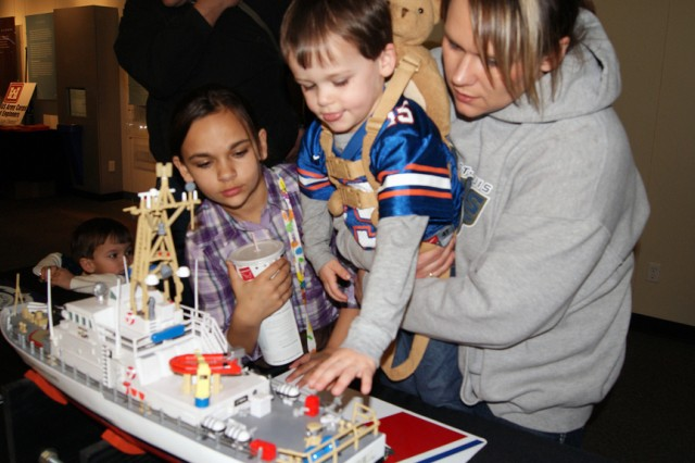 Children explore a model of a U.S. Coast Guard vessel as they learn about river navigation Feb. 25 during Engineer Week at the St. Louis Science Center. (U.S. Coast Guard photo)