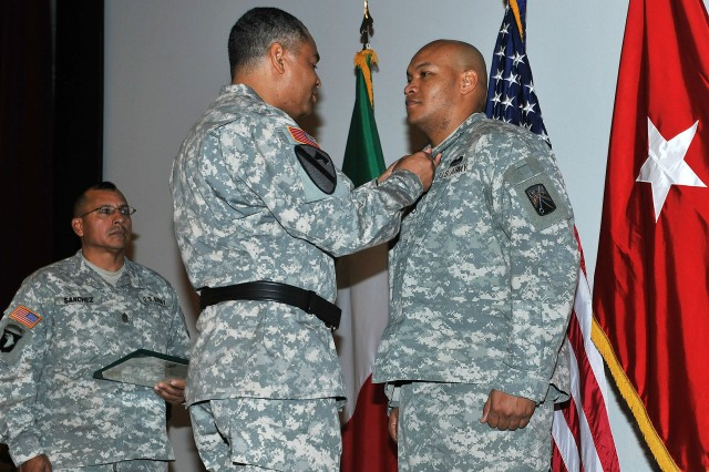 Brig. Gen. Aundre F. Piggee, the commanding general of the 21st Theater Sustainment Command, presents the Soldier's Medal to Staff Sgt. Eddie Peoples, a movement control specialist with the 386th Movement Control Battalion, 21st TSC-Italy, as Command Sgt. Maj. Michael Sanchez, the command sergeant major for the 21st TSC, readies the certificate for presentation at the Caserma Ederle Post Theater in Vicenza, Italy, Feb. 28, 2012. Peoples is commended for his actions on May 31, 2011, when he took an armed bank robber down after a heist in Sarasota, Fla.