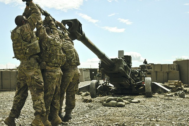 Soldiers of the 172nd Infantry Brigade in Afghanistan work at dislodging their M-777 155mm howitzer from a three-foot deep hole it dug after firing several projectiles. The huge weapon weighs 9,800 pounds and can launch projectiles more than 30 kilometers. picatinny engineers have developed a solution for Soldiers that makes the howitzer easier to maneuver. (Photo by Sgt. Ken Scar)