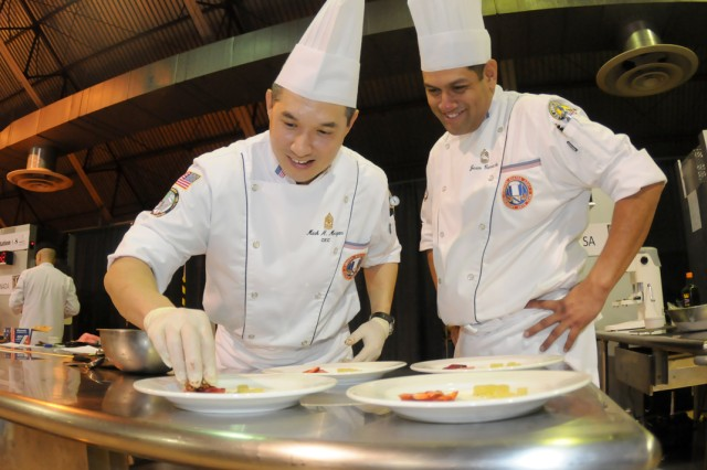 Sgt. Maj. Mark Morgan and Master Sgt. Jesus Camacho share a laugh during the heat of competition as Morgan touches up a dish during the international event of the Military Culinary Arts Competition Feb. 29.  The two, members of U.S. Army Culinary Arts Team, represented the United States against the Canadians and Germans.