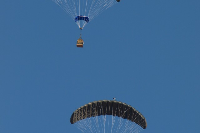 Parachutes employing the Joint Precision Airdrop System, or JPADS, drift toward earth above Yuma Proving Ground, Ariz.
