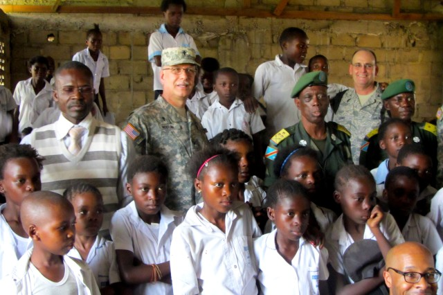 U.S. Army Africa Chaplain (Col.) John McGraw, along with Chaplain (Col.) Jeanne Paul Keela, chief of Democratic Republic of the Congo chaplains, and U.S. Africa Command Chaplain (Col.) Jerry Lewis, visit with students in a chapel school classroom in Kinshasa.