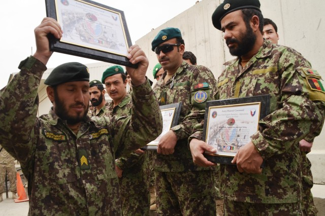 """An Afghan Soldier holds his certificate from a 45-day maintenance mentorship program over his head after proclaiming """"I serve Afghanistan"""" while other Soldiers who completed the program look on."""
