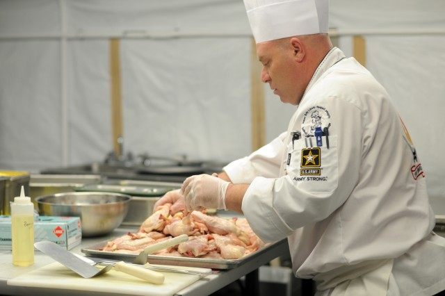 Cpl. Michael Fichman, part of the Fort Polk team, prepares the main entrée during the field competition at the 37th Annual Culinary Arts Competition, Feb. 9 - March 7, 2012, at Fort Lee, Va.