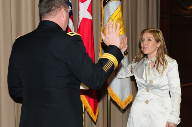 Maj.^Gen. Mark Yenter, Maneuver Support Center of Excellence and Fort Leonard Wood commanding general, administers the oath of office to Dr. Rebecca Johnson, deputy to the commanding general, during her promotion to a Tier II in the Senior Executive Service Friday.