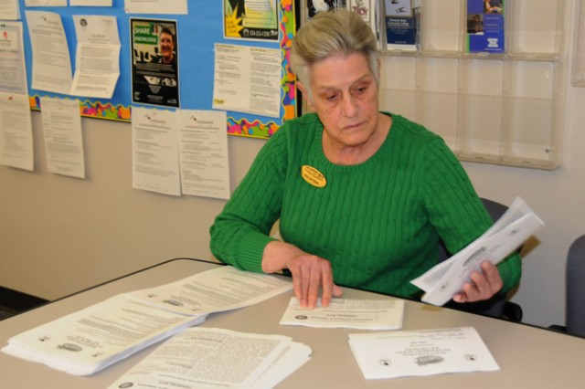 Joan Willingham, Army Community Service volunteer, folds newsletters at the Soldier Service Center.