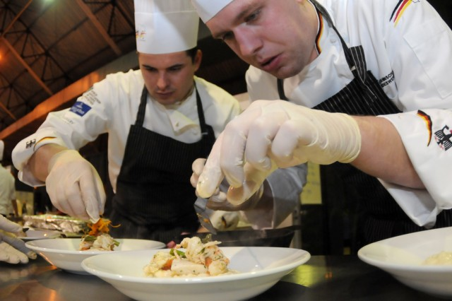 Staff Sgt. Patrick Stoye and Staff Sgt. Nils Vollmer, representing the German team, place food on plates during the four-course international category of the Military Culinary Arts Competition Feb. 29, 2012, at Fort Lee, Va.  The international category is new to the MCAC.