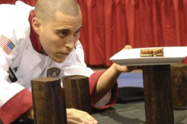 """Sgt. John Thomas, a member of the Fort Sill, Okla., team, carefully adjusts the alignment of a plate during a Team Buffet/Cold Food table display event early Saturday morning at the Post Field House on Fort Lee. Teams competing in the 37th Annual Culinary Arts Competition category had to """"demonstrate the beauty, skill and perfection of the culinary arts."""