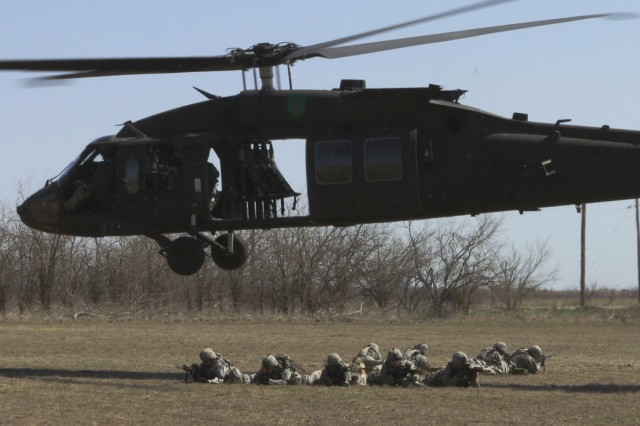 Nine Soldiers from 3rd Battalion, 13th Field Artillery keep their heads down after exiting a UH-60M Black Hawk. The Black Hawk was one of 14 helicopters from the 1st Combat Aviation Brigade, 1st Infantry Division out of Fort Riley, Kan. The Soldiers gained valuable experience working with the helicopters to prepare them for future missions.