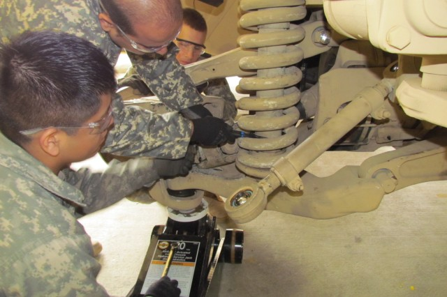 Wheeled Vehicle Mechanic School students crawl under an mine-resistant, ambush protected vehicle for maintenance lessons on its suspension system.