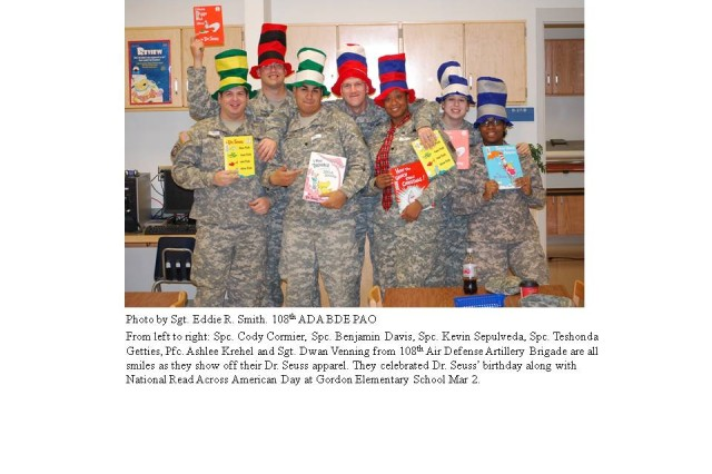 Spc. Cody Cormier, Spc. Benjamin Davis, Spc. Kevin Sepulveda, Spc. Teshonda Getties, Pfc. Ashlee Krehel and Sgt. Dwan Venning (from left to right) from 108th Air Defense Artillery Brigade are all smiles as they show off their Dr. Seuss apparel and books.