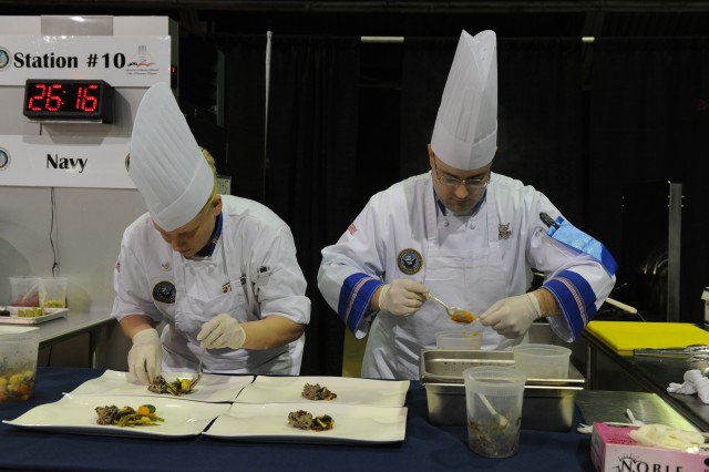 U.S.Navy Petty Officer 3rd Class Sondra Baier and U.S. Navy Culinary Specialist 1st Class with the Navy Culinary Team compose a dish for the Nutritional Hot-Food (Mystery Basket) competition in Fort Lee, Va., March 4, 2012. Chefs from each branch of the military competed in a various categories of the 37th Annual Military Culinary Competition. (U.S. Army photo by Spc. Daneille Hendrix)