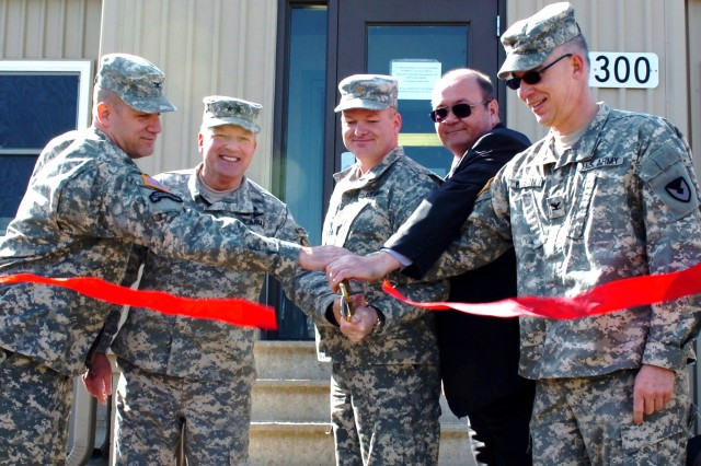 From left, Col. Ivon Denton, Camp Atterbury incoming garrison commander; Maj. Gen. Omer Tooley, commander, Muscatatuck Center for Complex Operations; Maj. Donald McGhghy, Army Sustainment Command liaison at Camp Atterbury, James Deloach, Deployment Operations program manager for Army Materiel Command, and  Col. Jeff Wilson, ASC Plans and Exercises, senior Guard adviser, share in the ribbon cutting March 1 establishing Camp Atterbury as the processing center for all contractors including non-LOGCAP (Logistics Civilian Augmentation Program) contractors deploying and redeploying. (Photo by Sgt. Will Hill)