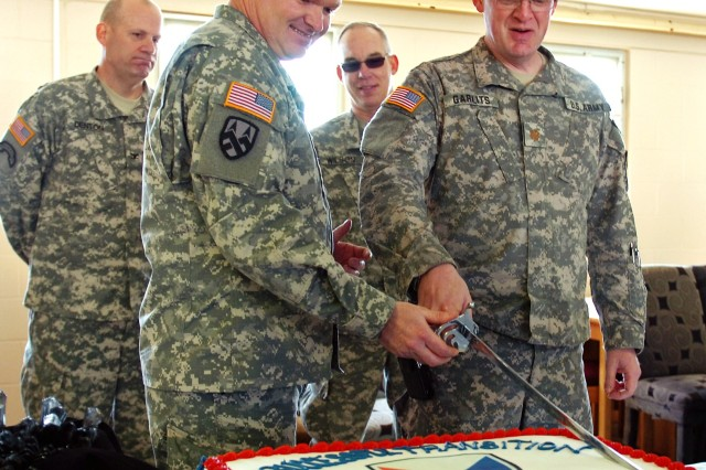 Maj. Donald McGhghy, Army Sustainment Command liaison at Camp Atterbury, and Maj. James Garlits, Individual Replacement Deployment Operation program manager, participate in ceremonial cake cutting at Camp Atterbury. (Photo by Sgt. Will Hill)