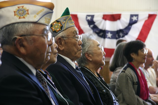 """MONTEREY, Calif. -- (Left to right) WWII Military Intelligence Service Nisei veterans George Tanaka and Ben Umeda watch as the Defense Language Institute Foreign Language Center Air Force Choir sings """"America the Beautiful"""" to conclude the Congressional Gold Medal Award Ceremony at the Monterey Peninsula Chapter of the  Japanese American Citizens League, in Monterey, Calif., March 4."""