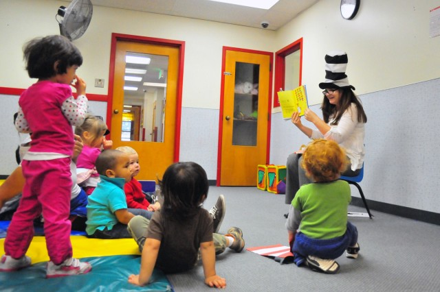 "PRESIDIO OF MONTEREY, Calif. -- MRCDC Director Elaine Vrolyks engages toddlers touching ""noses"" while reading a Dr. Seuss book."