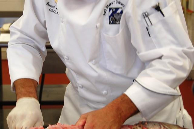 Sgt. Maj. David Turcotte, Fort Stewart, Ga., butchers a striped sea bass during the Armed Forces Chef of the Year event at the 37th Military Culinary Arts Competition at Fort Lee, Va. Turcotte was named Armed Forces Chef of the Year during the competition's award ceremony March 9.