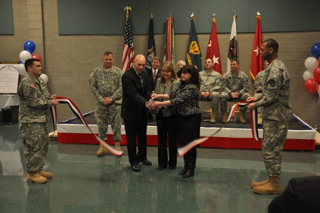 Laura Stultz (center), the wife of Army Reserve Chief Lt. Gen. Jack C. Stultz; Army Strong Community Center coordinators, Troy Klinge (left) and Debra Unseld (right), cut the ribbon signifying the grand opening of the fifth Army Strong Community Center at the Dr. Mary Walker U. S. Army Reserve Center, Walker, Mich., near Grand Rapids, Mich., March 3. The Army Strong Community Center connects those geographically dispersed Families with support resources in their own community. The center is an information and referral office dedicated to assisting and supporting service members, retirees, veterans, and Family members of all branches of the military, active and reserve. (U. S. Army Photo by Sgt. 1st Class Darrin McDufford.