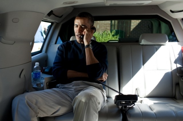 President Barack Obama talks on the phone with Afghanistan President Hamid Karzai from his vehicle outside the Jane E. Lawton Community Center in Chevy Chase, Maryland, March 11, 2012. The President called to express his shock and sadness over the reported killing of Afghan civilians.
