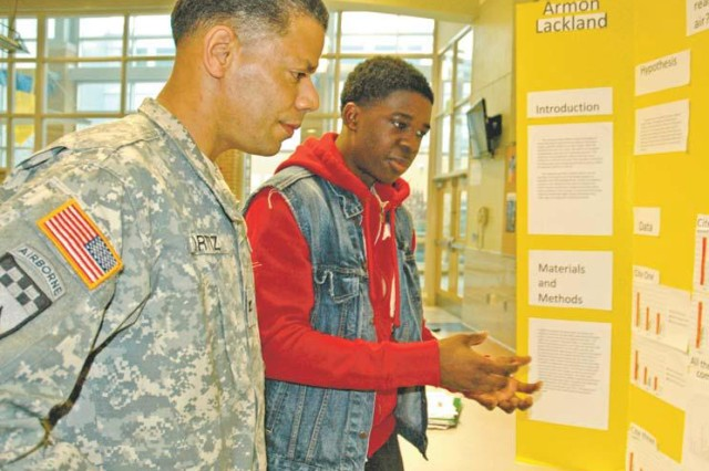 "APG Garrison Commander Col. Orlando Ortiz, (right) serving as a guest judge, discusses the project ""What's Really in Our Air"" with its creator, Aberdeen High School senior Armon Lackland during the school's annual STEM (Science, Technology, Engineering, and Mathematics) Fair Feb. 29. Aaron Simmons, chemistry teacher and STEM fair coordinator, said each student receives guidance from a mentor during the project. ""Every year we need volunteers to serve as mentors,"" Simmons said, ""especially local science professionals."" To volunteer, e-mail Simmons at aaron.simmons@ hcps.org."