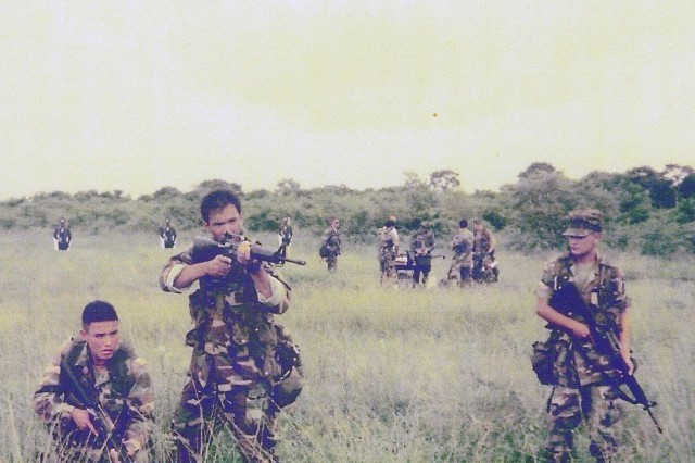 Then-Bolivian Army Cpl. Rodrigo Mendoza (left) watches as then-U.S. Army Sgt. 1st Class Patrick Fensom (center), of 7th Special Forces Group (Airborne), runs through a reaction-to-contact drill during a 1997 Joint Combined Exchange Training exercise in Bolivia with the country's Manchengo ranger battalion.