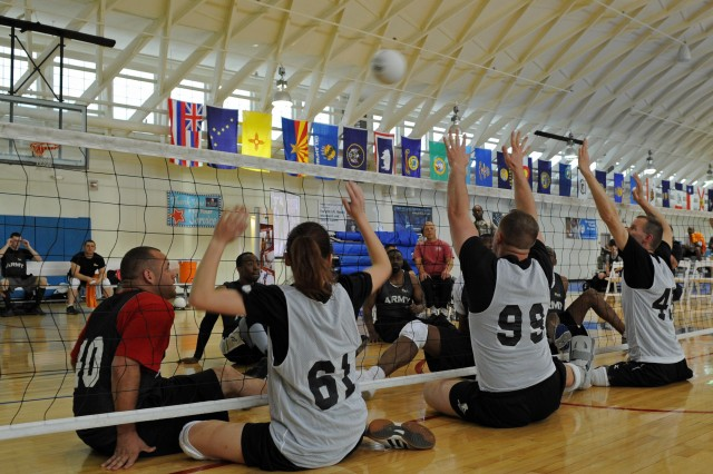 Fort Meade Warrior Transition Unit, in the shorts, who volunteered to play against competitors trying out for the 2012 Warrior Games in Colorado Springs, Colo., April 30 to May 5, play sitting volleyball in a clinic at Fort Meade Md.