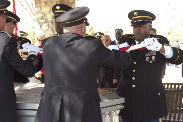 Pallbearers begin folding the American flag that rested on William O. Wooldridge's, the first sergeant major of the Army, casket during his interment at the Fort Bliss National Cemetery, Texas, March 13, 2012.