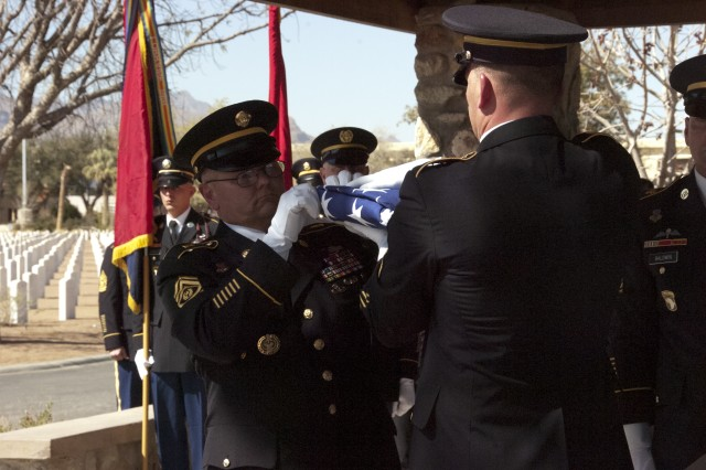 Command Sgt. Maj. Rory Malloy, commandant, U.S. Army Sergeants Major Academy, inspects the flag before accepting it and presenting it to the surviving spouse of William O. Wooldridge, the first sergeant major of the Army, during his interment at Fort Bliss National Cemetery, Texas, March 13, 2012.