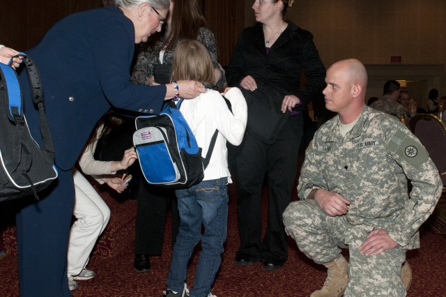 """Angel Elmer, the daughter of 316th ESC Soldier Spc. Jason Elmer, receives a """"Hero Bag"""" from the volunteer organization Operation Military Kids at the 316th ESC Yellow Ribbon Reintegration Program at the Wyndham Grand hotel in Pittsburgh on March 10.  Volunteers handed out backpacks to all of the children in attendance four-years-old and older.  For the children that were younger, they handed out blue teddy bears provided by the American Legion Auxiliary.  (Photo by Sgt. Peter J. Berardi)"""