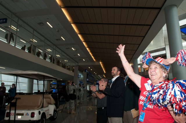 Linda Tinnerman (far right) and Medal of Honor recipient, former Army Staff Sgt. Salvatore Guinta (center) greet the final inbound Rest and Recuperation flight passengers to arrive at the Dallas/Fort Worth International Airport after the closure of the DFW personnel assistance point March 14, 2012.