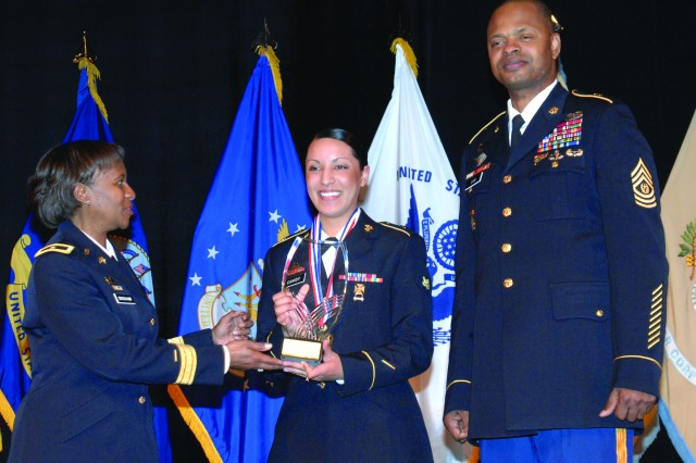 Brig. Gen. Gwen Bingham, Quartermaster School commandant, and Command Sgt. Maj. James Sims, school command sergeant major, award the Junior Chef of the Year trophy to Spc. Jacqueline Canidy from Fort Stewart, Ga.