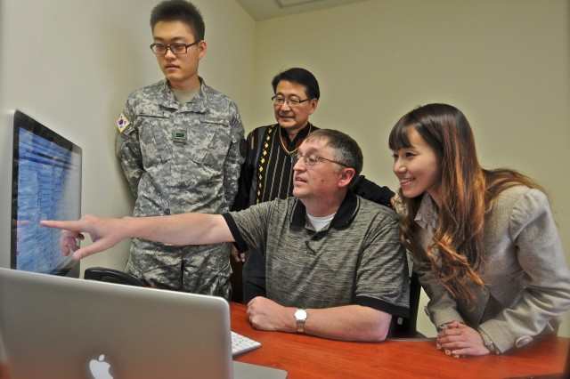 Cpl. Han, Je-ho (left), Chang, Sang-hyon (center back) and Mary Kim, (right) look on as Steven Hoover, command information chief, U.S. Army Garrison Humphreys, demonstrates the use of Hootsuite, to schedule posts to Facebook and Twitter. The Humphreys social media team was selected as the best in Army for 2011.