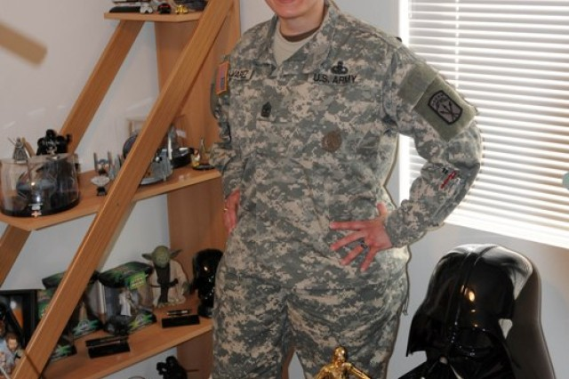 """LACEY, Wash.""""Sgt. Maj. Vic M. Alvarez from Bronx, N.Y., and administration and operations sergeant major for the Army Career and Alumni Program on Joint Base Lewis-McChord, stands with a few pieces of her large Star Wars collection at her home in Lacey, Wash., on Feb. 27."""