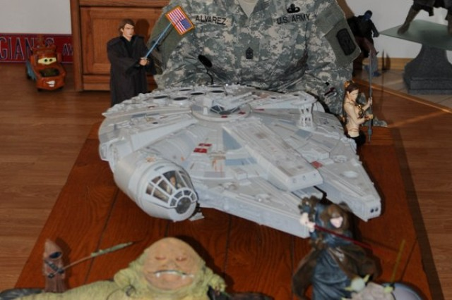 """LACEY, Wash.""""Sgt. Maj. Vic M. Alvarez from Bronx, N.Y., and administration and operations sergeant major for the Army Career and Alumni Program on Joint Base Lewis-McChord stands in her living room with a few pieces of her large Star Wars collection at her home in Lacey, Wash.,  on Feb. 27."""